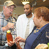 """Delbert Bailey, rertired coal miner, presented Stroud, with her grandson Jermaine, with some honey he said was """"sweet like her."""" Jon C. Hancock/for The Register-Herald"""