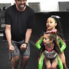 Adam Holsten, owner of GymFinity, left, works with, Marlee Wills, front, Amya Grasty, back, preparing his All-Star team called the Cosmo's for a traveling cheerleading competition. <br /> (Rick Barbero/The Register-Herald)