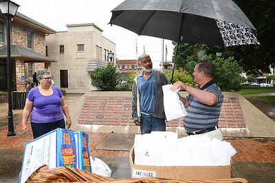 Joanne Carver, left and her husband, Mike Carver, Calvary Assembly of God church members, hand out free lunches to, Bland Lester, of Glen White at Shoemaker Square in Beckley Tuesday afternoon. They set up every third and fifth tuesday from 11 am to 1 p.m. during the month and serve, hotdogs, sandwiches, chips, fruit snacks and water to the homeless. (Rick Barbero/The Register-Herald)