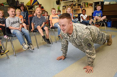 Wesley Bowling, Army National Guard Specialist, demostrates to students at Lester Elementary School about some of his physical training he does for the Guard during the schools Career Day. Students rotated every 10 minutes and listened to nine vendors speak about their careers. (Rick Barbero/The Register-Herald)