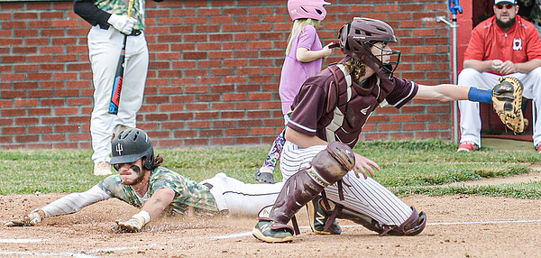 F. Brian Ferguson/Register-Herald Oak Hill's Zane Wolfe slides into home ahead of the ball to Woodrow Wilson catcher Micah clay during Tuesday action in Oak Hill.