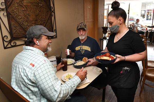 Amanda Syner, waitress at Giuseppe's Restaurant on Main Street in Mt. Hope, serves Michael Kessinger, left, and Virgil Kincaid.<br /> Rick Barbero/The Register-Herald)