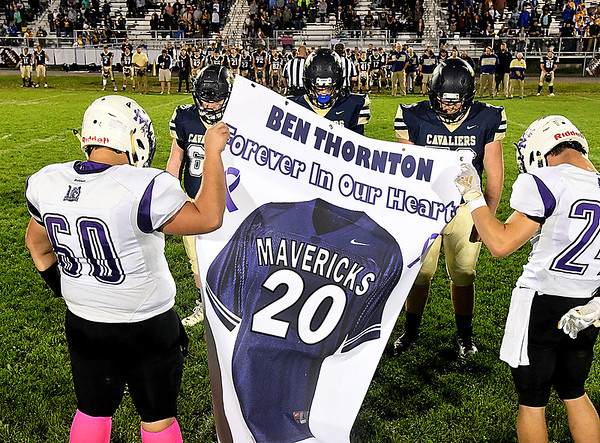 Greenbrier West team presented a banner to James Monroe players honoring Ben Thornton, former James Monroe coach who recently died. Both teams and fans bowed their heads in prayer honoring Thornton before the begining of the the game Friday night at Greenbrier West High School.<br /> (Rick Barbero/The Register-Herald)