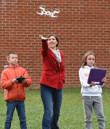 Taylor Ray, third grade teacher at Sophia Soak Creek Elementary School, center, helps lift a drone in the air operating by Ethan Sullivan, left and Lacey Goodson, right, monitors the drone with an iPad.