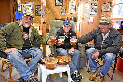 """(Brad Davis/The Register-Herald) Home brewers (from left) Dave Bieri, Wayne Baker and James Bogle offer cheers to the camera as they pose for a quick photo Sunday afternoon in Bieri's garage, where they and others have begun gathering to brew, share recipes and try new takes on existing ones as part of a """"Craft Beer Club"""" of sorts."""