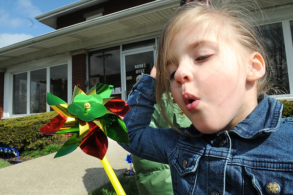 Haleigh Deck, pre-school student at Raleigh County Head Start, blows on a pinwheels during a program held in front of the Mayors office on South Kanawha Street. Rob Rappold, the Mayor of Beckley, proclaimed April Child Abuse Prevention Month for the City of Beckley.  Just For Kids Child Advocacy Center organized the 5th Annual Plant a Pinwheel for Prevention event on the Mayor's lawn.  Over 30 children from the Raleigh County Head Start Center came and helped the Mayor and two Deputies from the Sheriff's Dept. plant pinwheels.<br /> (Rick Barbero/The Register-Herald)