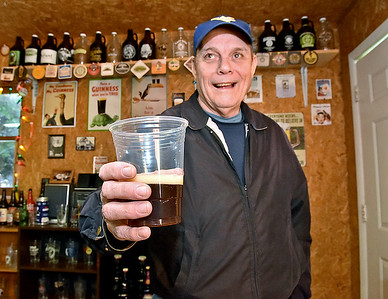 (Brad Davis/The Register-Herald) Home brewer Wayne Baker shows off his creation that is basically a copy of the Sam Adams Winter Lager, but with his own additions and twists during a Craft Beer Club gathering in friend Dave Bieri's garage Sunday afternoon.