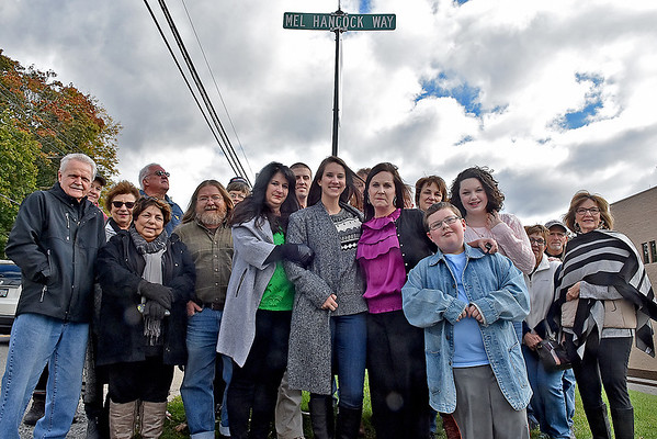 (Brad Davis/The Register-Herald) A group of friends and family led by his wife Tammy (middle in green), son Chris (left of Tammy) daughters Ann Elizabeth (right of Tammy) and Alisa Evans (2nd from right of Tammy), among others, pose for a quick photo at the entrance of what's now known as Mel Hancock Way following a brief ceremony for the late Beckley resident Saturday afternoon.