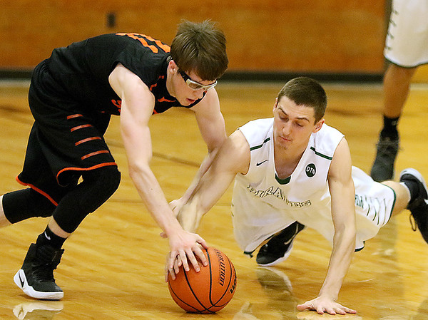 (Brad Davis/The Register-Herald) Summers County's Logan Jones and Fayetteville's Dalton Dempsey dive for a loose ball during Class A Boys Region 3 Co-Final Thursday night at the Soldiers & Sailors Memorial.