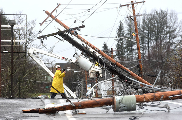 Workers evaluate the scene on East Main Street in Oak Hill, WV where six power poles went down after a group of powerful storms pushed their way across the state around 10:30 a.m. Linemen on the scene said homes and businesses serviced by those lines would be without power for at least 24 hours.<br /> (Rick Barbero/The Register-Herald)