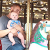 Axle Baisen takes his first ride on a merry-go-round with his father Kenneth Baisen on opening day of the State Fair of West Virginia in Fairlea Thursday. Jenny Harnish/The Register-Herald