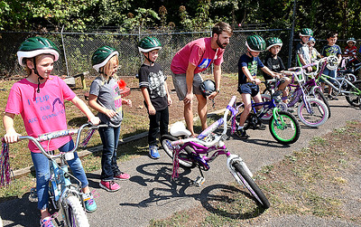 Andy Davis, pedestrian and bike trail cordinator Active Southern West Virginia, 4th from right, talks with childern in Tammy Darnell's second grade class at Mt. Hope Elementary School, during a bike saftely rodeo.  (Rick Barbero/The Register-Herald)