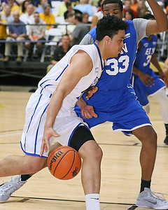 (Brad Davis/The Register-Herald) Mid-State Ford's (Class AAA) T.J.Wood, left, drives to the basket against EIN's (National) L.J. Bryan during the Scott Brown Classic Saturday night at the Beckley-Raleigh County Convention Center.