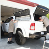Mike Goode, left, and George Duarte, installers for Leonard Building Truck & Accessories on 3788 Robert C Byrd Drive in Beckley, helping, install a new top on a truck.<br /> (Rick Barbero/THe Register-Herald)