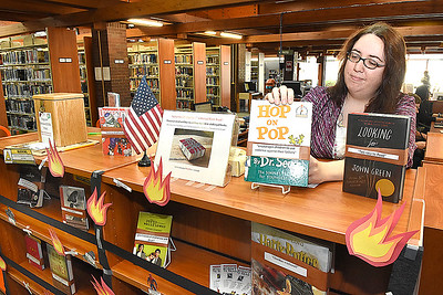 Amy Stover, director Raleigh County Public Library in Beckley, places a Dr. Seuss book on the library's challenged book display. (Rick Barbero/The Register-Herald)