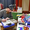(Brad Davis/The Register-Herald) Princeton-based artist Trey Snyder hangs out and works on another of his signature hand-drawn portraits as he mans a table full of crochet work by his wife Anna, who runs Anna's Crochet Enterprise inside the Raleigh Playhouse & Theatre during yesterday's Small Business Saturday event.