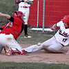 (Brad Davis/The Register-Herald) Oak Hill baserunner Kade Legg scores a run after an errant throw to Liberty catcher Timmy Daniels skips loose on what should have been a force out with the bases loaded during the 4th inning of the second game of a doubleheader Friday evening in Oak Hill.