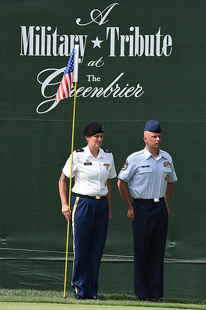 Ssg. Kyra Vance, WV Army National Guard, left and MSgt. Kevin Cordle, WV Air National Guard holds the flag stick while golfers putt out on the par 3, 18th green during the first round of, A Military Tribute at The Greenbrier golf tournament.<br /> (Rick Barbero/The Register-Herald)