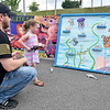 (Brad Davis/The Register-Herald) Dad James assists as his four-year-old daughter Alexis angles for sharks at a fishing game during the Kid's Quest Carnival Saturday morning at Marquee Cinemas.