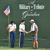(Brad Davis/The Register-Herald) Military members greet caddies as they hold the American flag serving as the pin marker on no. 18 during opening round action of the Military Tribute at The Greenbrier Thursday afternoon in White Sulphur Springs.
