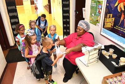 Sheryl Mitchell, cafetera manager Crescent Elementary School in Beckley, hands out breakfast to student during the first day of school in Raleigh County. (Rick Barbero/The Register-Herald)