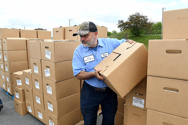 Dean Norris, Beckley Housing Authority, load boxes of food during Farmers to Families food giveaway held Friday from noon until 4 p.m. at the Beckley-Raleigh County Convention Center. 1200 boxes of food that was supplied contain fresh produce, meat and dairy products.<br /> (Rick Barbero/The Register-Herald)