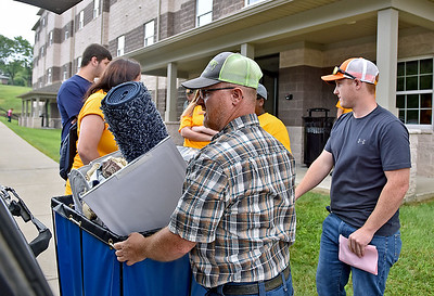 (Brad Davis/The Register-Herald) WVU Tech parent Nathan Morris, left, helps son Kevin, right, load belongings into a cart to take up to his dorm at University Hall during move-in day Sunday morning.