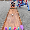 (Brad Davis/The Register-Herald) Three-year-old Meadow Bridge resident Parker Schoolcraft gets help in aiming his shot from Spiderman as he plays a mini bowling game, one of a few movie characters on hand during the Kid's Quest Carnival Saturday morning at Marquee Cinemas.