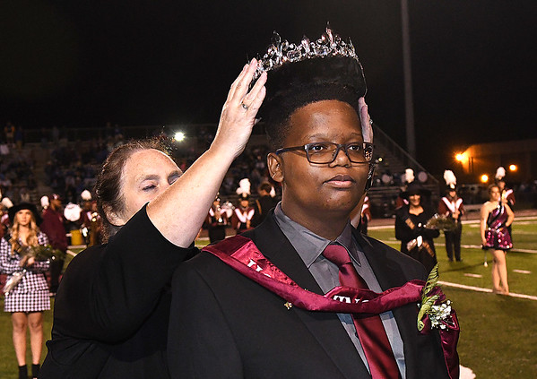 Coach Pam Shrader, left, crowns Gravely Nickoles king during the homecoming presentation at halftime of the Woodrow Wilson vs Princeton Friday night at VanMeter Stadium in Beckley.<br /> (Rick Barbero/The Register-Herald)