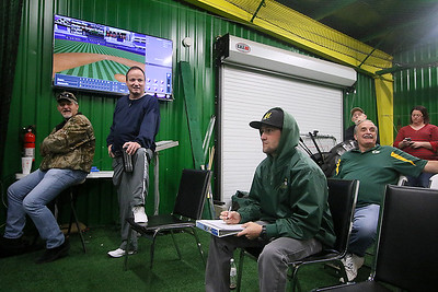 Brad Davis/The Register-Herald West Virginia Miners manager and Upper Deck owner Tim Epling (2nd from left) hangs out behind the plate area where scorers keep track and players' parents and family members can watch the games Sunday afternoon.