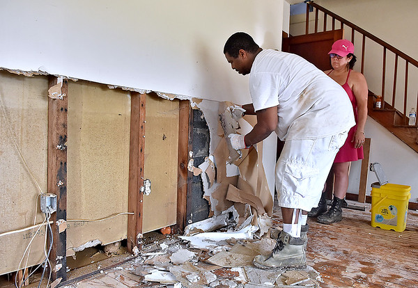 (Brad Davis/The Register-Herald) Washington Street resident Roy Grimes' daughter Brin Terry, right, looks on as her husband Daryl tears out waterlogged drywall Sunday afternoon in Alderson. The two spent the day helping Grimes with the cleanup process.