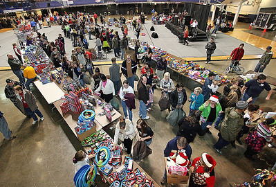 Brad Davis/The Register-Herald Hundreds of shoppers and volunteers buzz around the floor area of the Beckley-Raleigh County Convention Center Saturday morning during another successful Mac's Toy Fund Party.