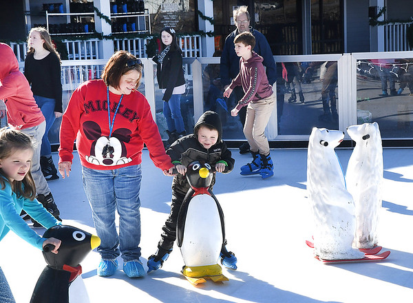 Crystal Welch, left and her son Jacob Welch, 5, of Glen Daniels helps him as he skates in the rink located in front of the Beckley Exhibition Coal Mine Monday afternoon. The rink wil be open everyday through December 8 with exception of Thanksgiving Day.<br /> (Rick Barbero/The Register-Herald)