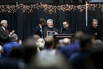 Recipients of the 32nd Annual Spirit of Beckley Award Greg Darby, center, and Cory Beasley, right, get the award from YMCA of Southern West Virginia CEO Jay Rist as the crowd stands and applauds at the Beckley-Raleigh County Convention Center in Beckley on Monday. (Chris Jackson/The Register-Herald)