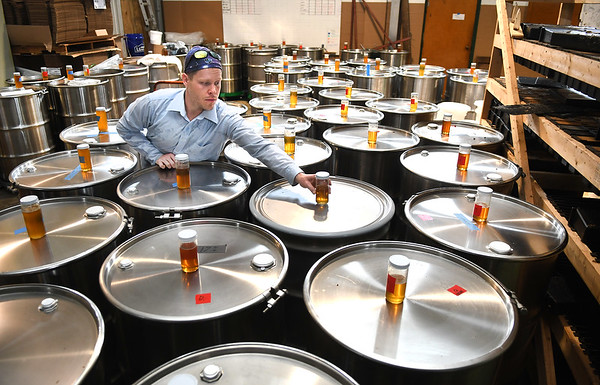 Clinton Taylor, of Appalachian Headwaters, placing samples of honey on the 55 gallon barrels at Camp Waldo in Hinton<br /> (Rick Barbero/The Register-Herald)