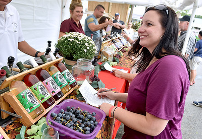 (Brad Davis/The Register-Herald) Pittsburgh, Pa. resident Sam Aaron takes notes on her favorite samples to track them down in the on-site shop at the Kirkwood Wine Festival Sunday afternoon in Summersville.