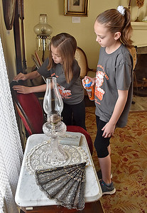 (Brad Davis/The Register-Herald) Bradley Elementary 5th graders and student council members Lainey Pack, left, and partner Kylie Norris make sure to get every inch as they clean in the library of Wildwood House during a Spring cleanup Saturday afternoon.