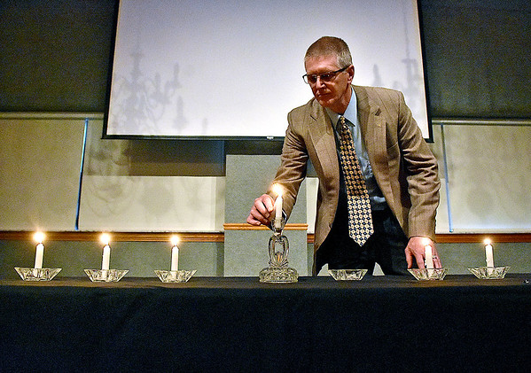 (Brad Davis/The Register-Herald) Tom Sopher lights the 7th candle representing all others who died along with the six million Jews murdered during the holocaust at the conclusion of this year's Yom HaShoah ceremony held every year in Beckley Sunday afternoon inside WVU Tech's Carter Hall.