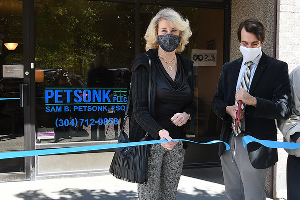 Sam Petsonk, employee lawyer, right, cuts ribbon with Denise Southern, membership development director Chamber of Commerce opening, for the grand opening of his new office on 223 Main Street in Beckley.<br /> (Rick Barbero/The Register-Herald)