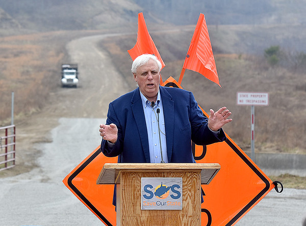 (Brad Davis/The Register-Herald) Governor Jim Justice outlines his ambitious plans for continuing work on the unfinished Coalfields Expressway, seen in the background, as well other road projects and plans for tackling the state's budget crisis during a Save Our State press conference and presentation Sunday afternoon.