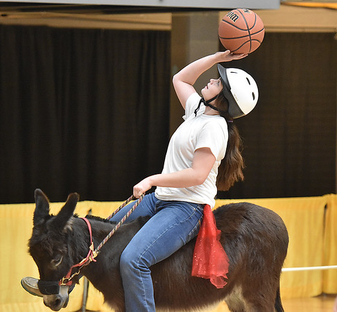 (Brad Davis/The Register-Herald) Madison Deck gets her donkey in position for a shot as her team, the Honky Tonk Badonka Dunkers, take on The Hee Haw Gang during a donkey basketball tournament to benefit the Raleigh County Horseman's Association Sunday afternoon at the Beckley-Raleigh County Convention Center. The rules are simple, as it's basically standard basketball, but you must be on your donkey when taking a shot. You can dismount to pick up a loose ball or move around the court quicker, but you must have your donkey in tow at all times when not riding it. RCHA hopes to have a few more of these events in the future.