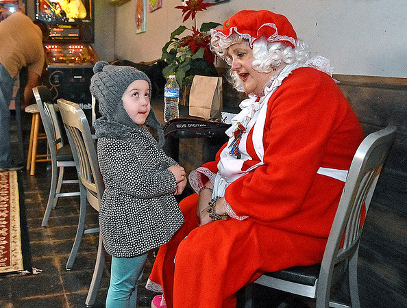 (Brad Davis/The Register-Herald) Four-year-old Reese Morgan has a conversation with Mrs. Claus, who was on hand with Santa at Brown Dog Bottom during yesterday's Small Business Saturday event.