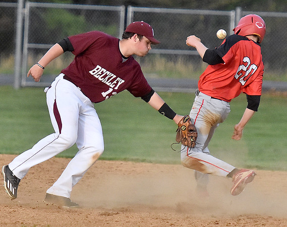 (Brad Davis/The Register-Herald) Woodrow Wilson shortstop Michael Maiolo makes the tag on St. Albans' Travis Atkins as he tries to steal 2nd, but the ball pops out as he pulls his glove over during the Flying Eagles' loss to St. Albans Friday evening in Beckley.