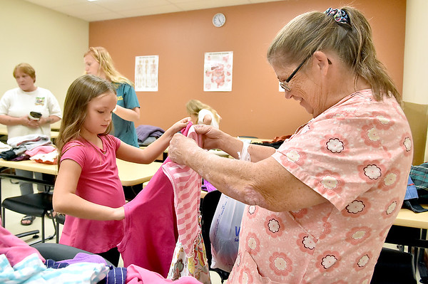 (Brad Davis/The Register-Herald) Seven-year-old Isabella Hodge picks out clothes with Grandmother Chris Garrison during Valley College's Day of Caring Saturday afternoon on the Beckley Campus. The event provided clothing, shoes, backpacks and school supplies to kids between the ages of four and 17, and food items to their families.
