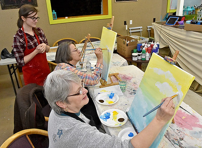 """(Brad Davis/The Register-Herald) Mt. Hope residents Ramona Brown, right, and Dolly Lilly spend a Sunday painting what will eventually be a scene of hot air balloons in an afternoon sky using acrylics on canvas as instructor Lynsi Boyd helps them with tips and tricks during a studio painting session at 110 Marshall in Beckley. The art studio and music venue usually has similar paiting parties on Friday nights scattered throughout the year, including some Sundays. Painting sessions are often themed in a variety of ways designed to help painters build skills in painting certain types of objects or textures, with yesterday's being """"Up, Up an Away"""" in reference to the balloons. Similar upcoming painting events will be """"Peaceful River"""" on Monday, March 27 at 6:00 p.m. and """"Angel Wings"""" Friday, April 7 at 6 p.m. Keep an eye on their facebook page or give them a call at 304-634-8367."""