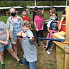 Classmates at Midland Trail Middle school watch Evan Adkins getting the feel for weight difference using three different bows for archery and Jaxon Barnhouse during WVU Adventure School held at the Summit Bechtel Reserve in Glen Jean.<br /> (Rick Barbero/The Register-Herald)
