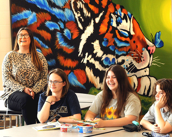 Shady Spring High School art teacher Melissa Losada, Serenity Brooks, Sydney Harper, and Madison Day, sit in the cafeteria and talk about the fun they all had painting two 10' x 7' canvases that will hang in the school. Jon C. Hancock/for The Register-Herald