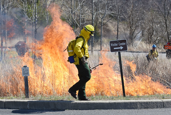 A crew member with the Beckley Fire Department walks away after setting a blaze tall grass during the NPS conducts a prescribed burn at the Sandstone Visitor Center as part of the New River Gorge National River Thursday. The annual burn was slower this year to let more wooded invasive species of plants burn away, said Dave Bieri, with the NPS. (Chris Jackson/The Register-Herald)