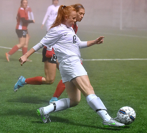 (Brad Davis/The Register-Herald) WVU Tech's Ruby Bingham sends the ball towards the Rio Grande net as she's pursued by defender Cassidy Young (#13) during a foggy Wednesday night at the YMCA Paul Cline Memorial Sports Complex.