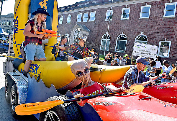 (Brad Davis/The Register-Herald) WVU tech students aboard the Tech Adventures float paddle and spray their way along Kanawha Street during the school's homecoming parade Saturday morning in Beckley.